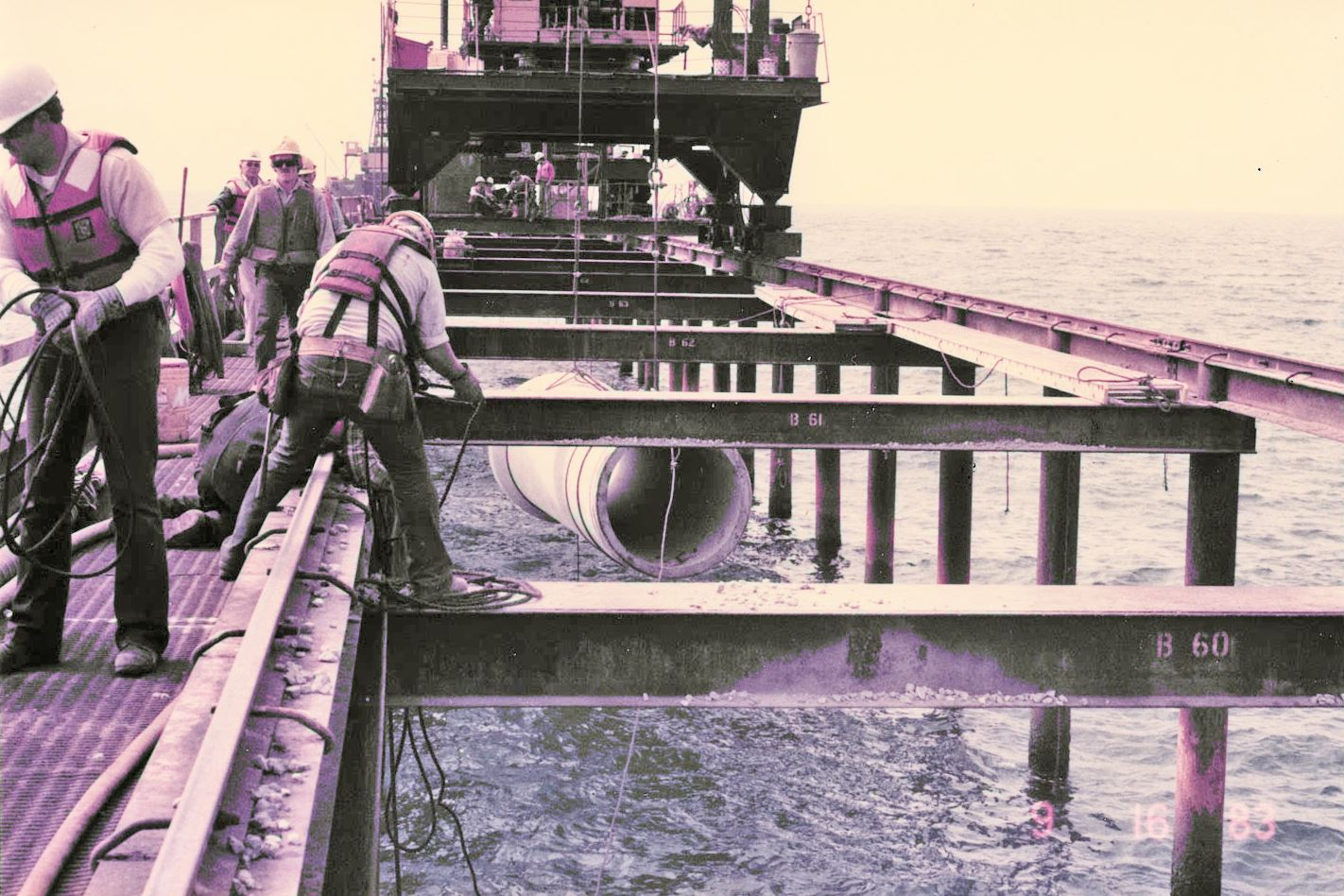 Crew aboard ship use machinery to lower the outfall pipeline into the Pacific Ocean